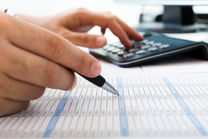 Two hands, one holding a pen and the other punching figures into a calculator, hover over an accounting sheet.