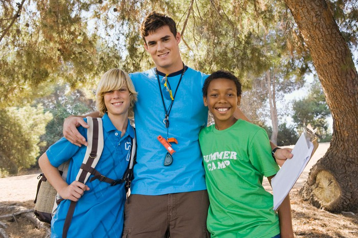 A camp counselor is shown with two kids.