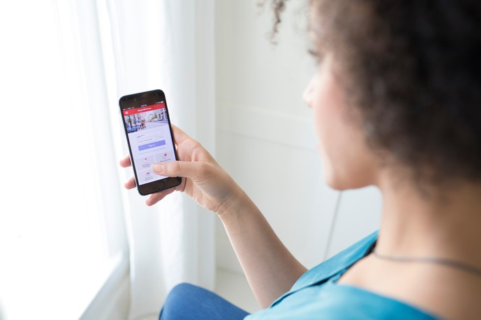 Woman using smartphone with Bank of America mobile app.