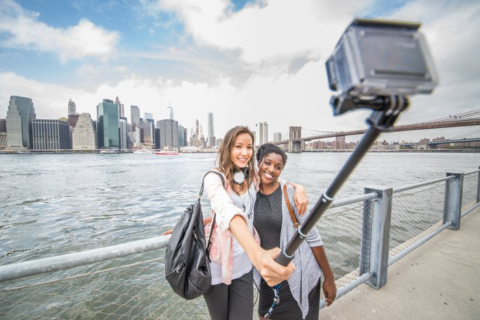 Two female friends taking a selfie in New York City with a GoPro camera attached to a selfie stick..