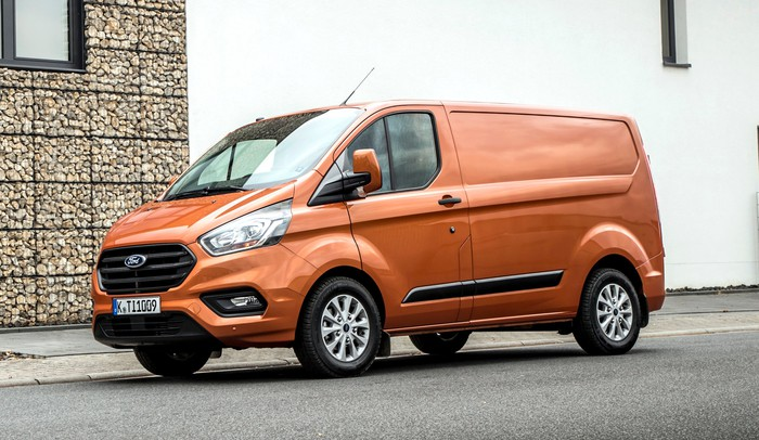An orange 2018 Ford Transit Custom, a commercial van about the length of a midsize sedan, on a European street