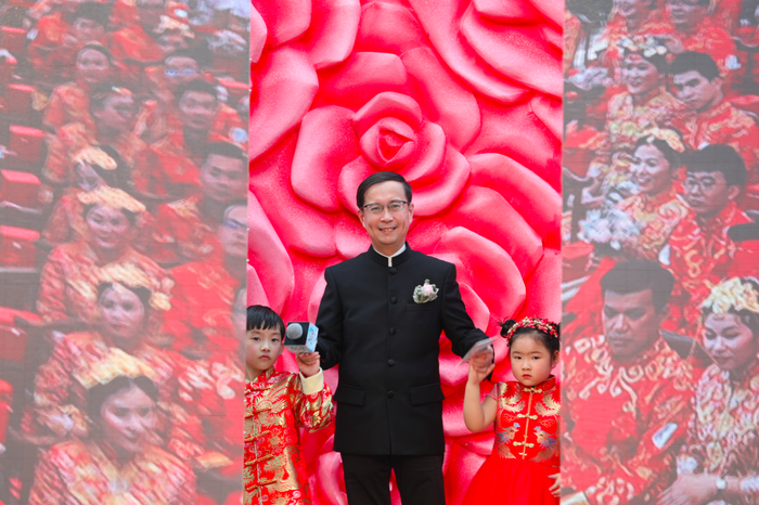Alibaba CEO Daniel Zhang stands with a little girl and a little boy who are both wearing decorative red outfits during Ali-Day