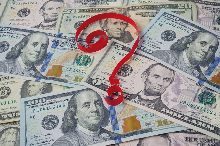 Red ribbon forming question mark on top of pile of $5, $10, $20, and $100 bills