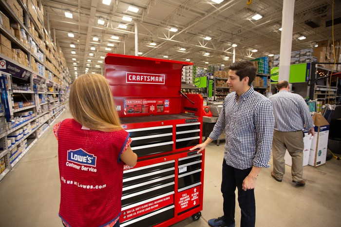 A Lowe's employee and a customer looking at a Craftsman tool storage unit in a Lowe's store.