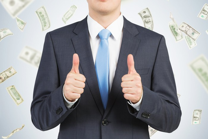 A person in a suit giving two thumbs up as cash money falls in the background.