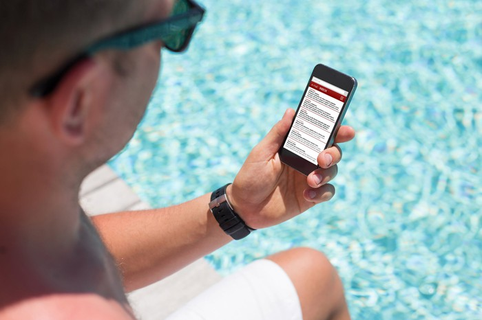 Man checking a mobile phone by a pool