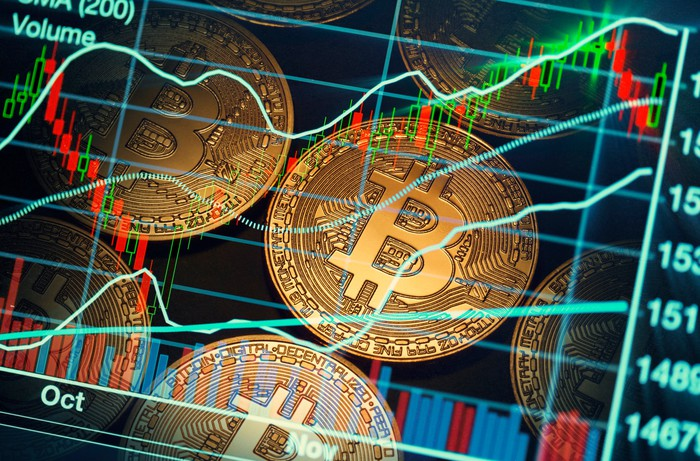 A stock chart is superimposed on several Bitcoin symbols.