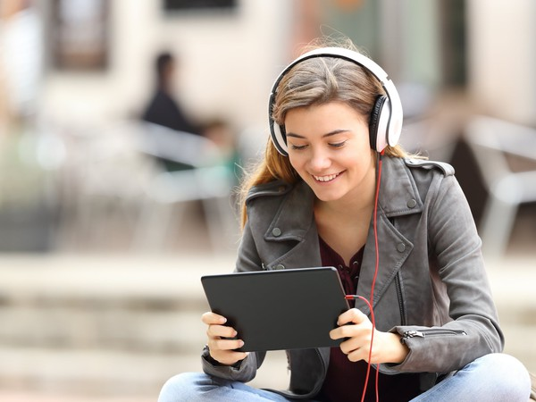 Streaming -- girl sitting wearing headphones smiling and looking at tablet