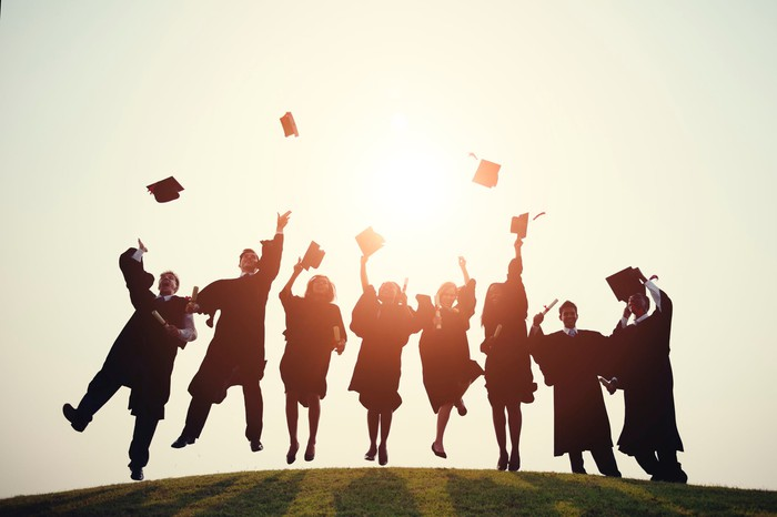 Graduates throw their hats in the air.