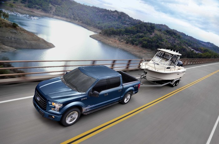 A blue Ford F-150 towing a boat.