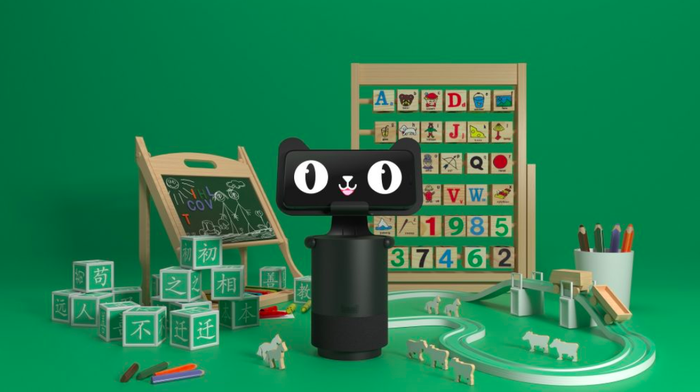 Alibaba's smart speaker, the Tmall Genie, is pictured with its new visual component and surrounded by educational toys against a green backdrop