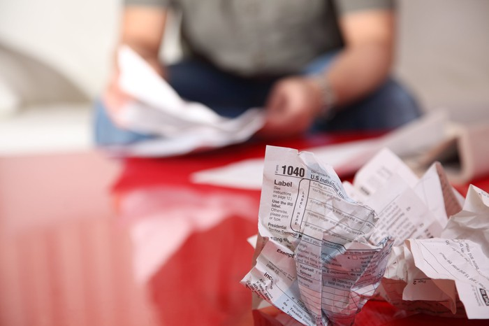 A crumpled up tax form on a table, with a man overlooking other tax forms in the background.