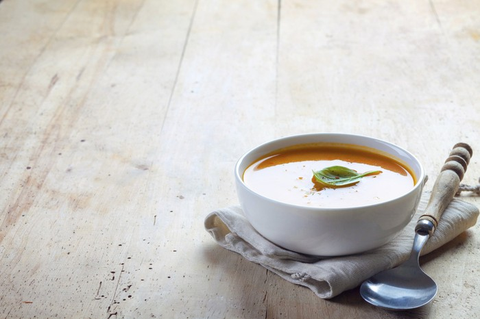 A bowl of soup on a table.