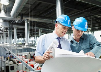 17_07_17 Business men looking at blueprints over factory floor_GettyImages-85406271