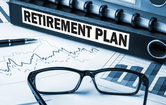 Binder with a label on it that says retirement plan, lying next to a pen and a pair of black glasses.