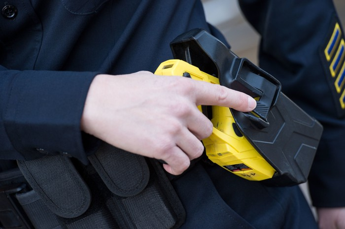 A taser being removed from its holster.