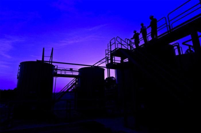 Three backlit workers at dusk on a railed walkway over an energy storage and pipeline facility.