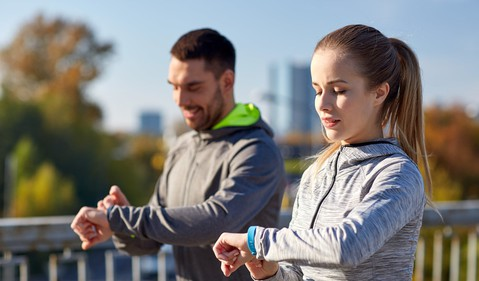 Image 2 Two people check their fitness trackers