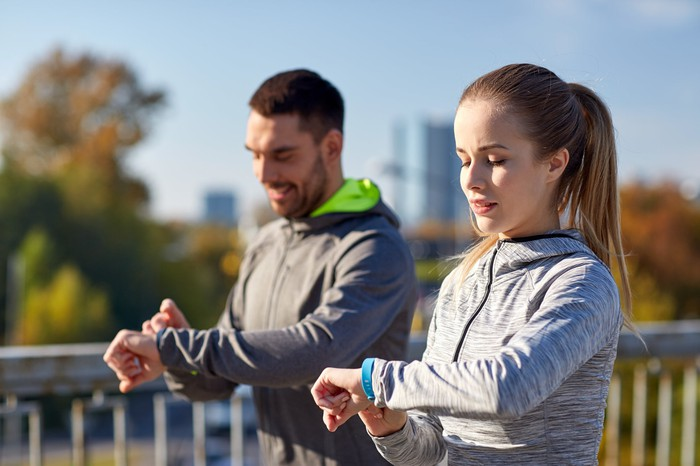 Two people check their fitness trackers.
