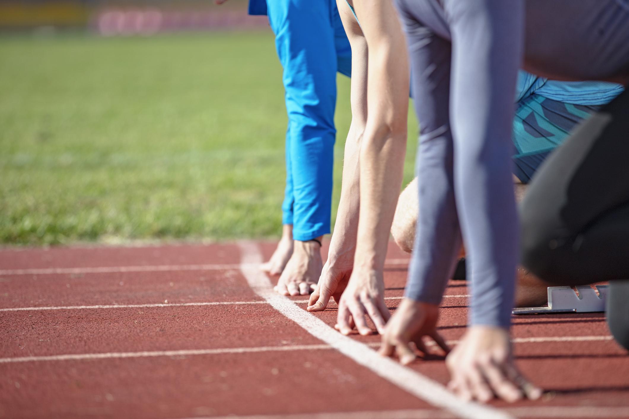 Three runners on starting blocks.