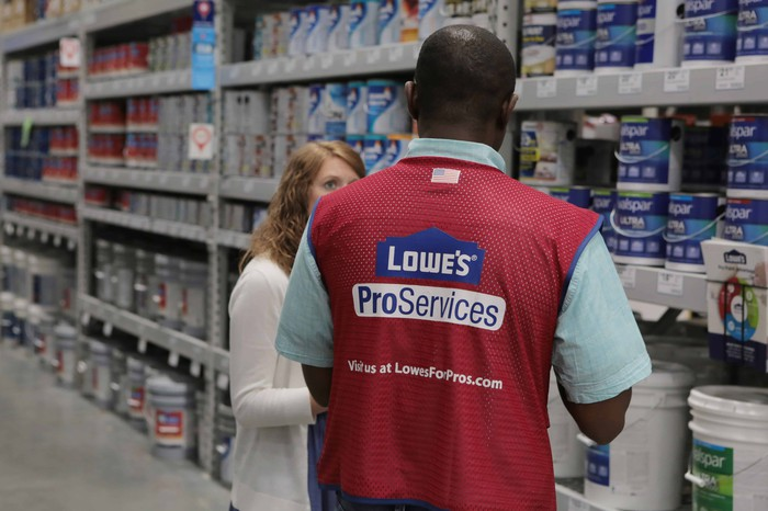 Lowe's employee helping woman in paint department