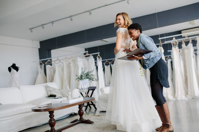 Woman wearing a wedding dress in a bridal shop with another woman standing behind her