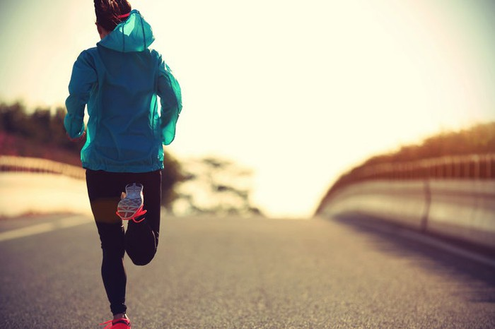A woman in fitness gear running down a road.