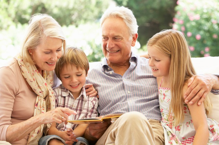 Grandparents reading to two young grandchildren.