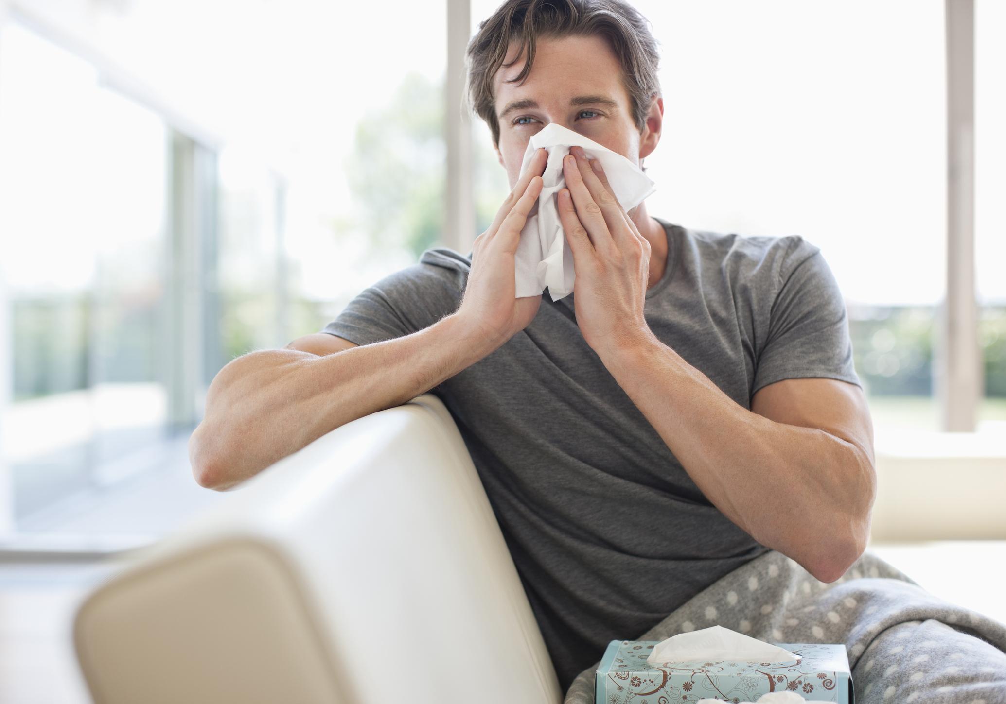 Man in pajamas blowing his nose