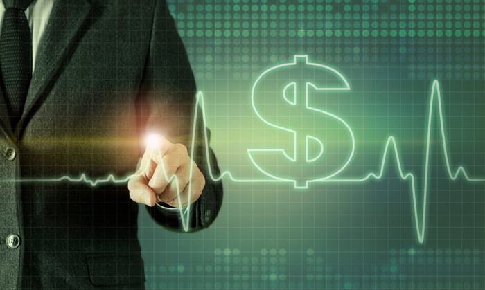 Businessman touching screen displaying heartbeat line and dollar symbol