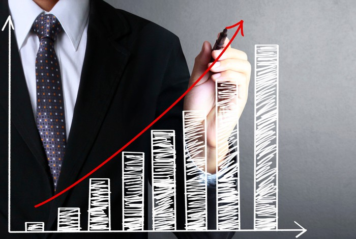 A person in a suit drawing a red line to show the upward trend of a white bar chart.