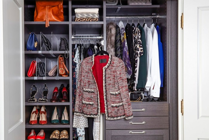 Closet organizational system with clothes hanging, shoes put away, and accessories placed in convenient locations.