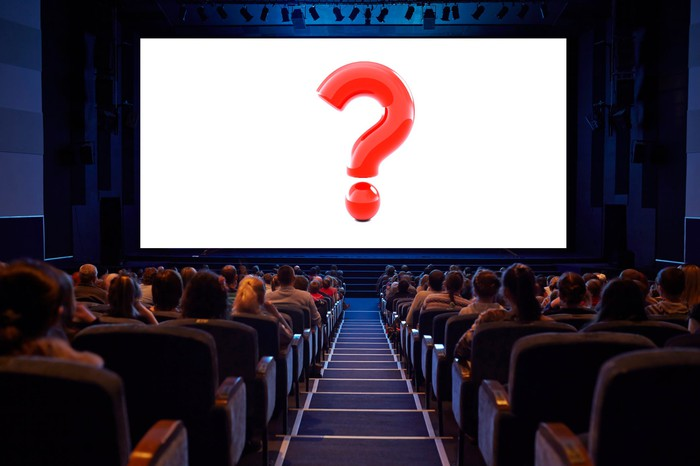A packed movie theater with a red question mark filling the silver screen.