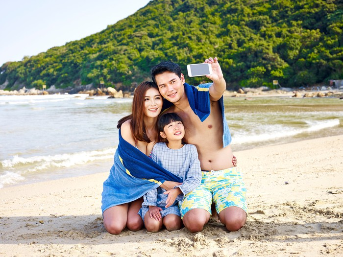 Man, woman, and child taking a selfie together on beach