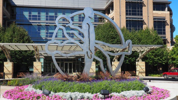 Metal sculpture of three human figures in circle, one prone, one reclined, and one standing, in a garden of flowers in front of an office building.