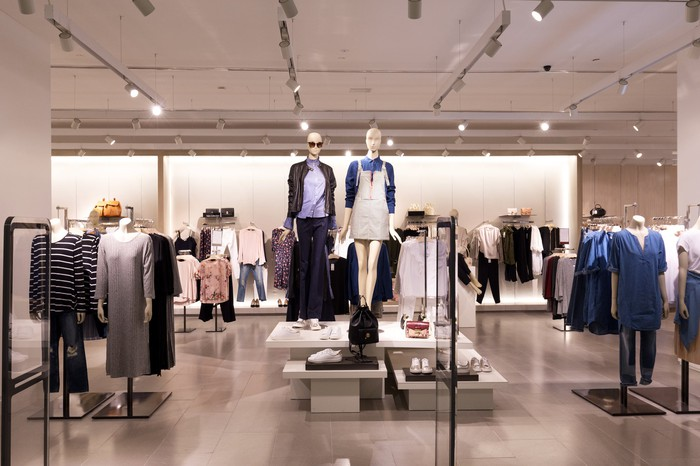Front of a premium apparel store with dressed mannequins on display.