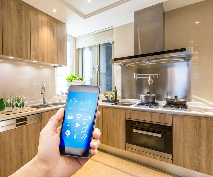A person controlling appliances and lights in a kitchen using a smartphone.