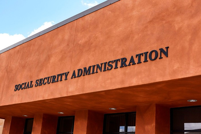 Brown stucco building with Social Security Administration on the side above glass doors.