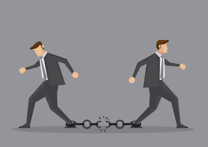 Two cartoon-style businessmen trying to walk away from each other, snapping a chain attached to their ankles.
