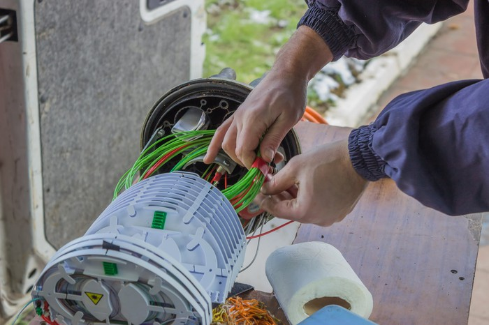 A technician works on a bundle of fiber-optic networking cables next to an outdoors connection hub.