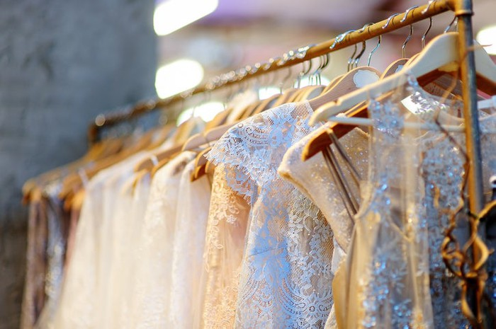 Close-up of wedding dresses on vintage clothing rack.