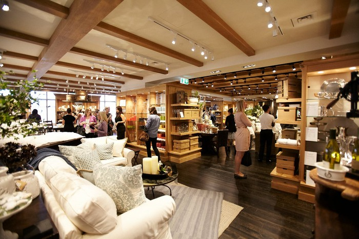 Interior of a Pottery Barn store with wood floors and ceiling beams