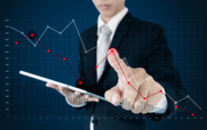 Man tracing falling stock graph with finger.