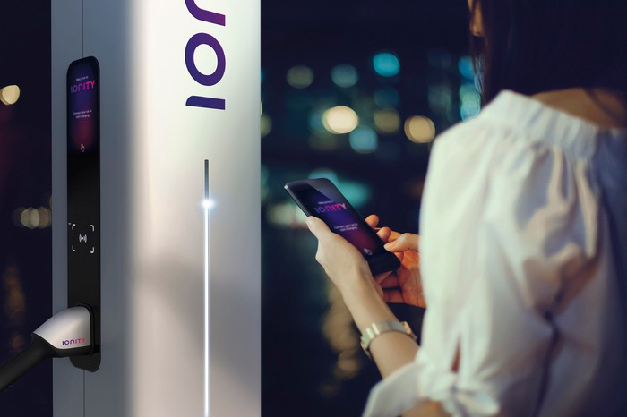 A woman is standing next to an Ionity charger, holding a cellphone displaying the company's app.