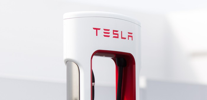 The top of a Tesla Supercharger, a white object shaped somewhat like a sleek gas pump, with Tesla's logo visible in red.