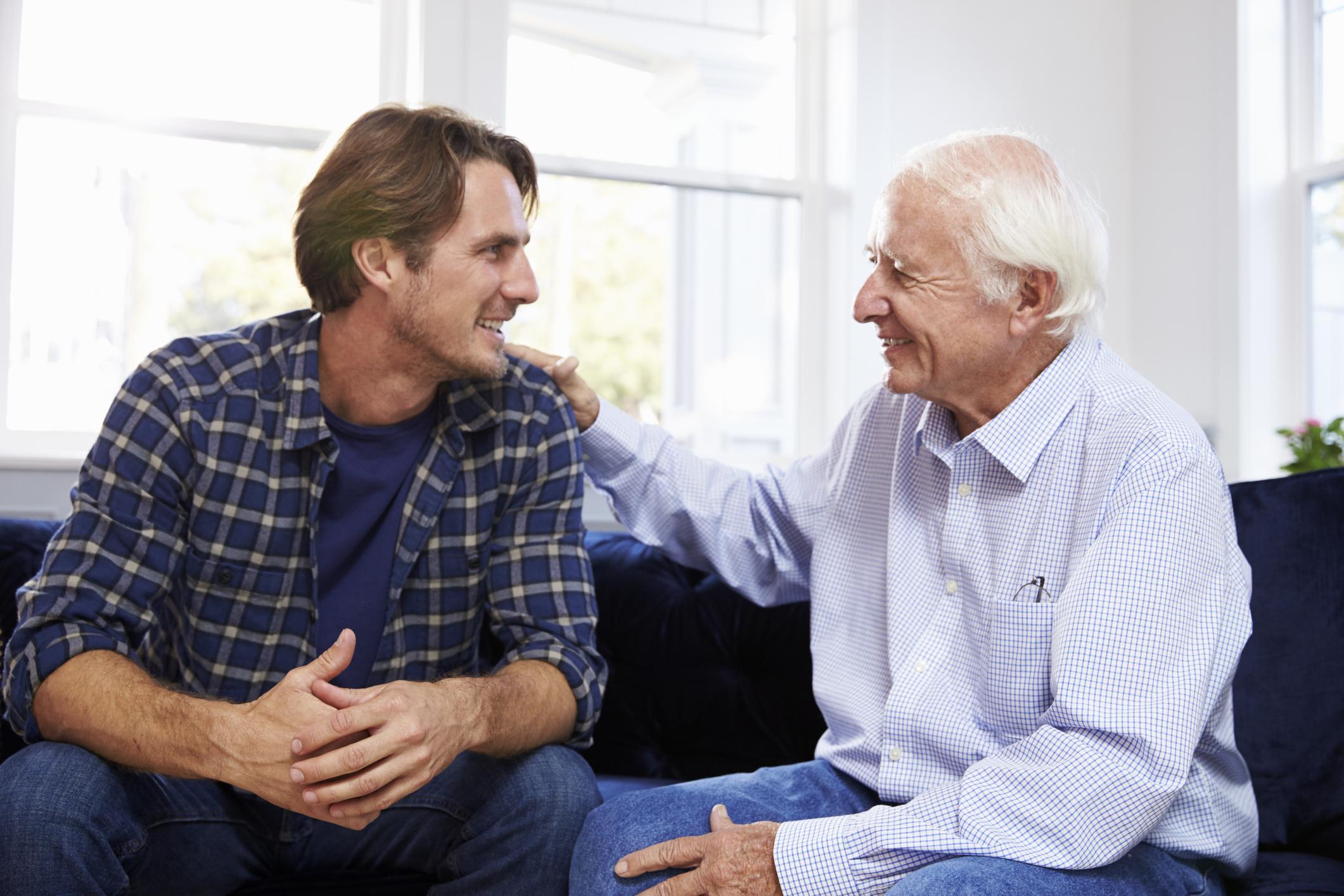 Older man patting younger man on the shoulder