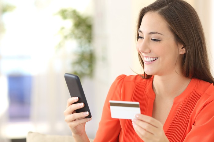 Woman in a red blouse smiles at her phone while holding a credit card in her other hand.