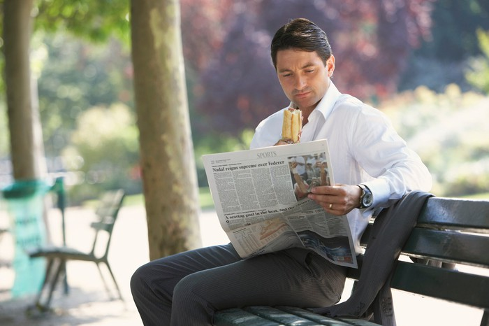 Man in professional clothing reading a newspaper on an outdoor bench while holding a sandwich.