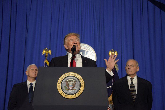 President Trump on a podium, with Vice President Mike Spence and Chief of Staff John Kelly behind him.