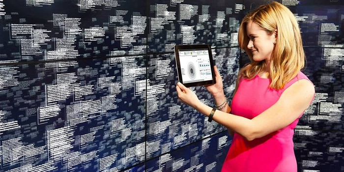 A woman holding a tablet up to a wall filled with digital cloud data.